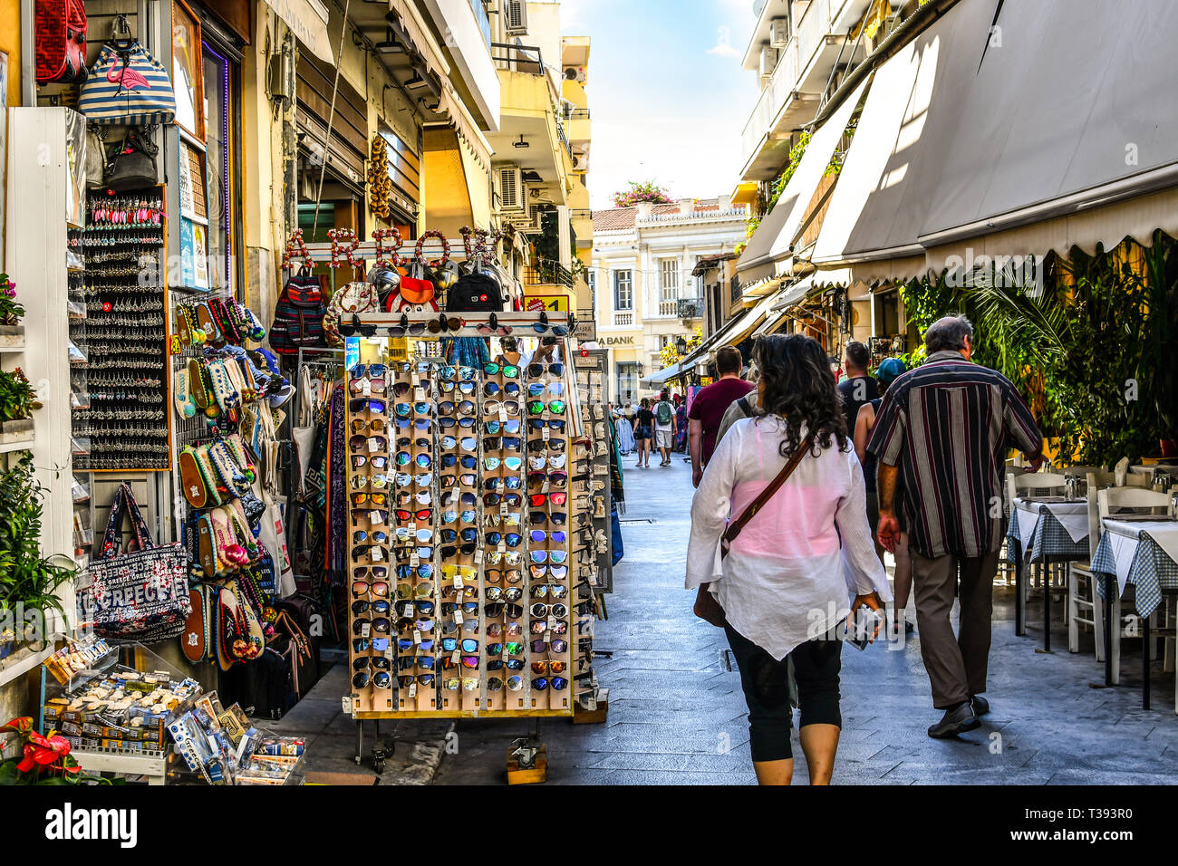Tourists walk the narrow path between souvenir shops and outdoor vendors selling gifts in the touristic Plaka section of Athens, Greece. Stock Photo