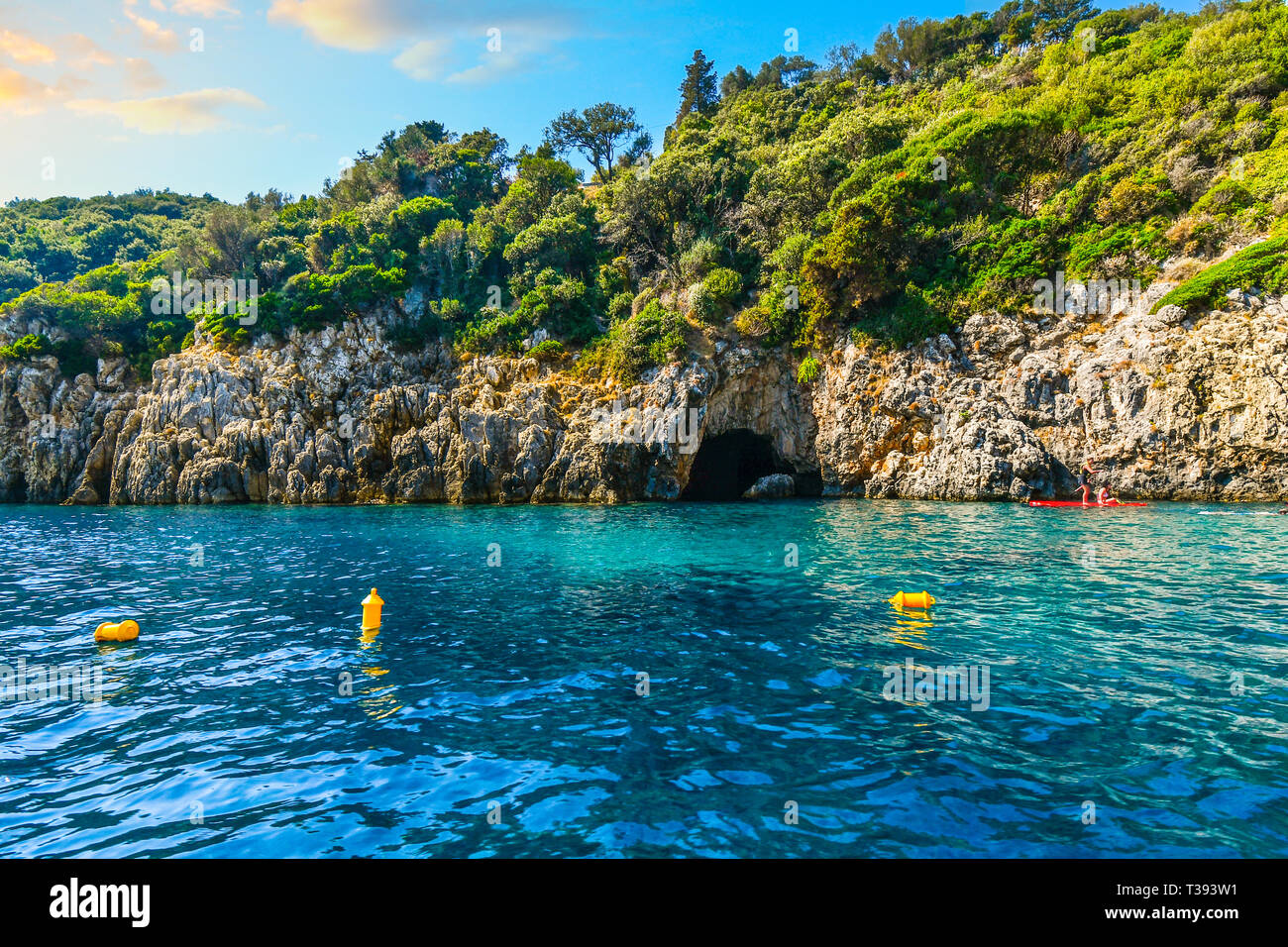 Two young women paddle board past the blue cave on the coast of the Greek island of Corfu on the Aegean Sea Stock Photo