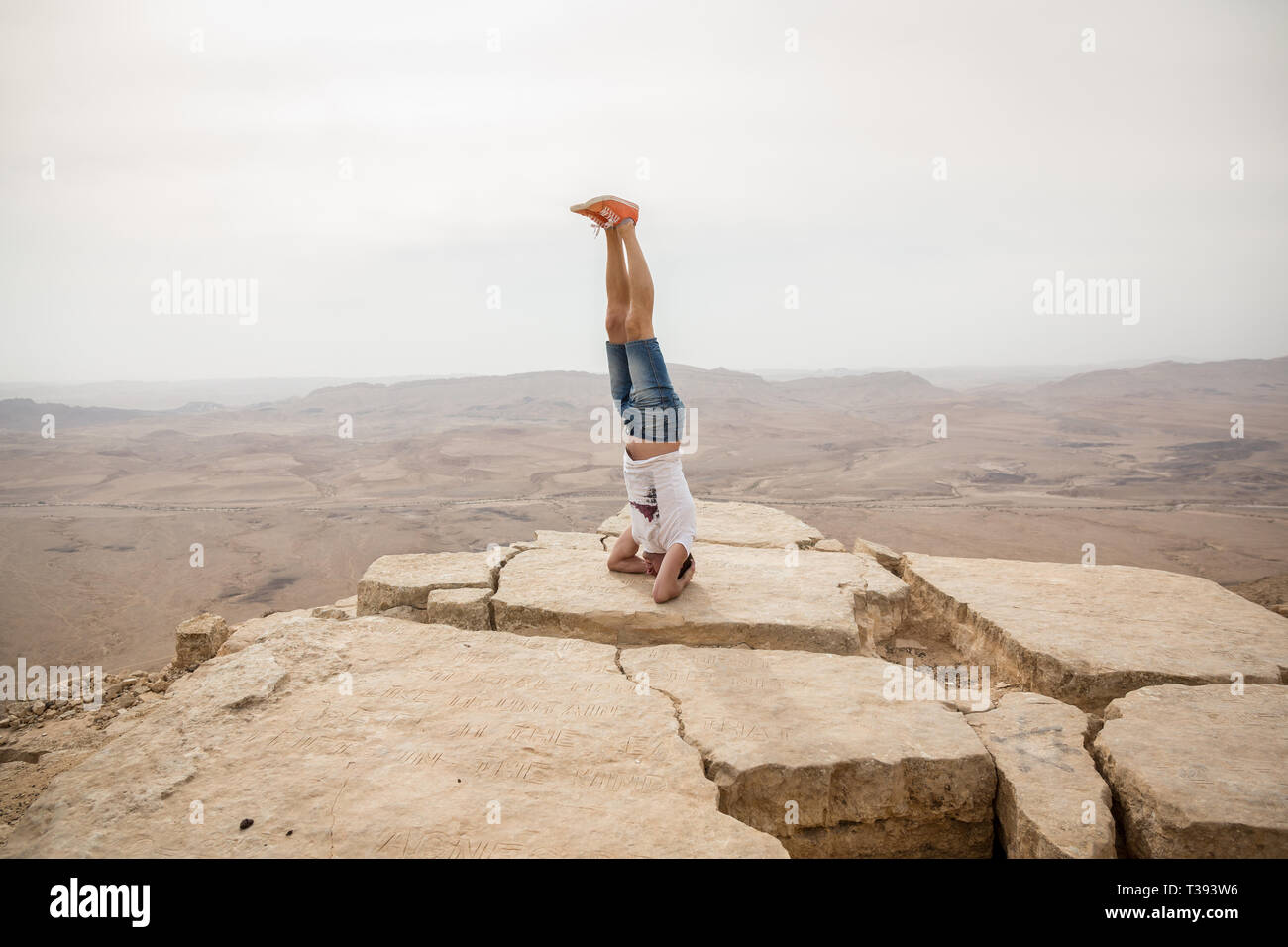 Mitzpe Ramon, Israel - 22 november, 2016: Man standing on his dead on the edge of Ramon crater cliff at  Negev desert, Israel Stock Photo