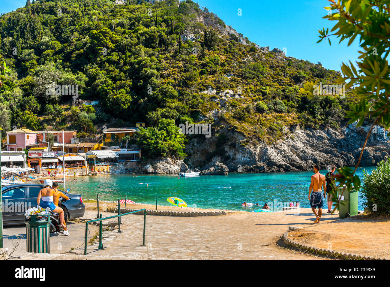 A young couple on a motorcycle arrive at a small bay near Palaiokastritsa Beach on the Greek island of Corfu. Stock Photo
