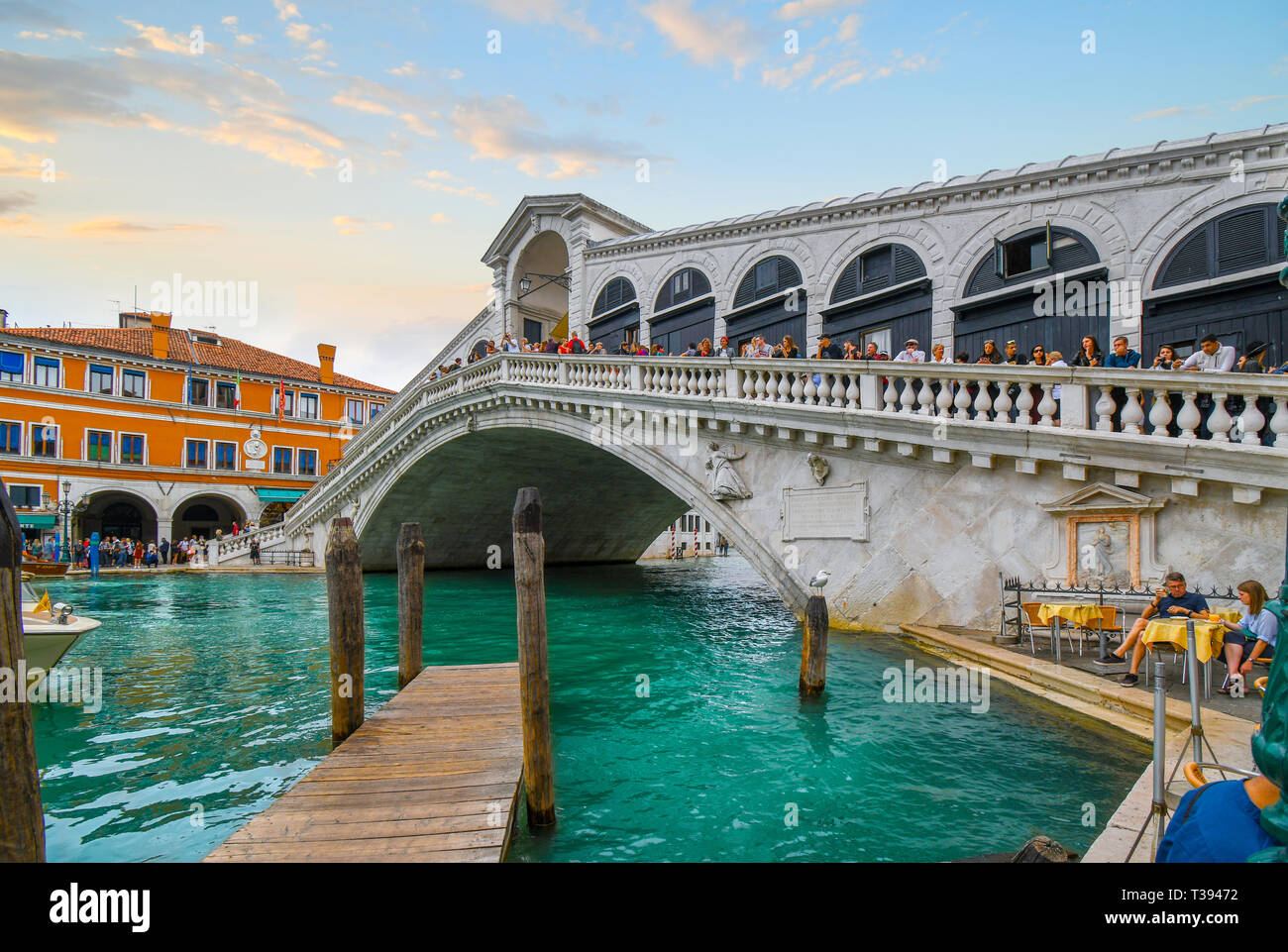 Tourists line the Rialto Bridge overlooking the Grand Canal as a sea gull perches on a pier and watches a couple dine at a cafe in Venice, Italy Stock Photo