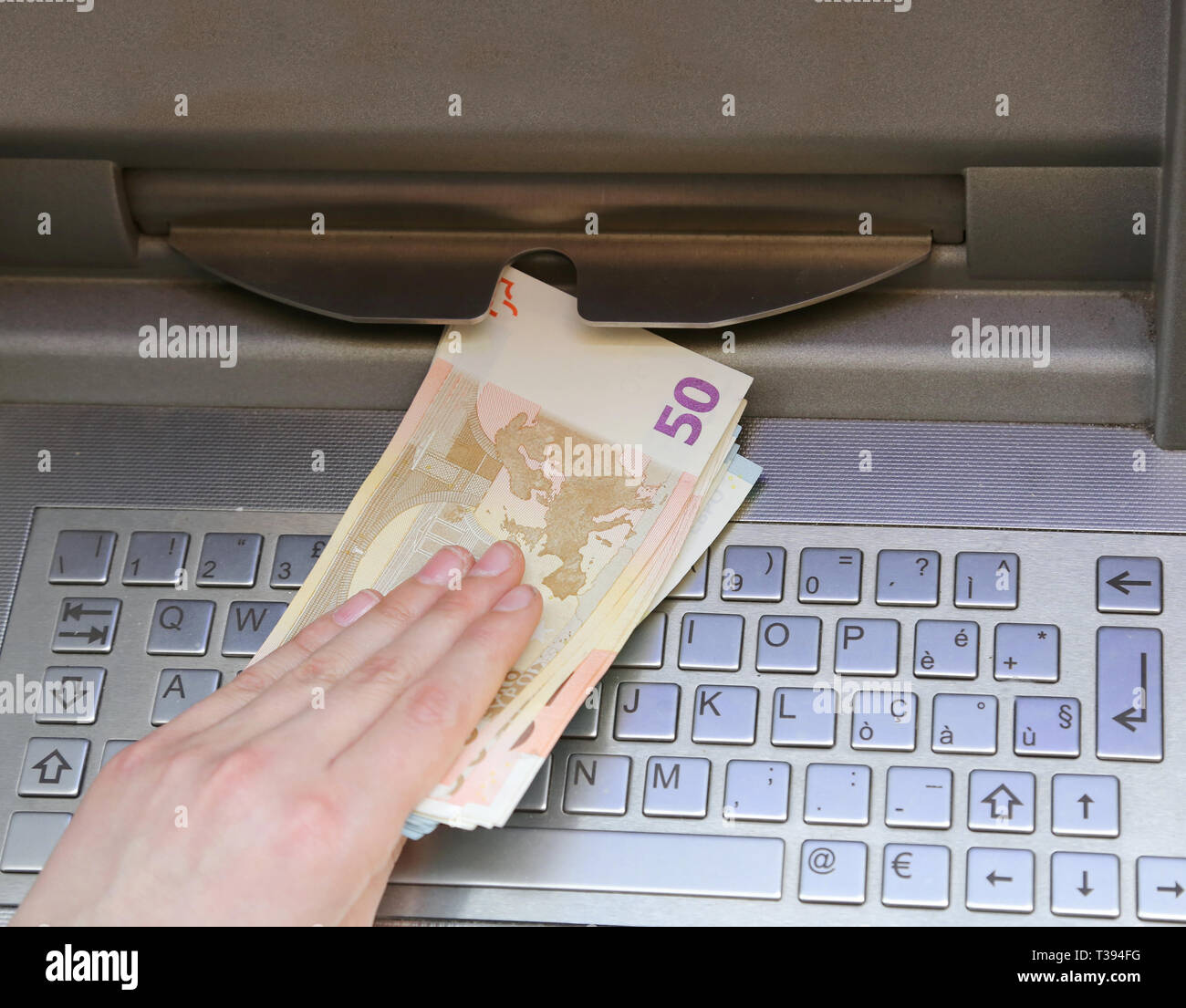 hand that withdraws banknotes of 50 euros from an ATM of a European bank - Stock Image