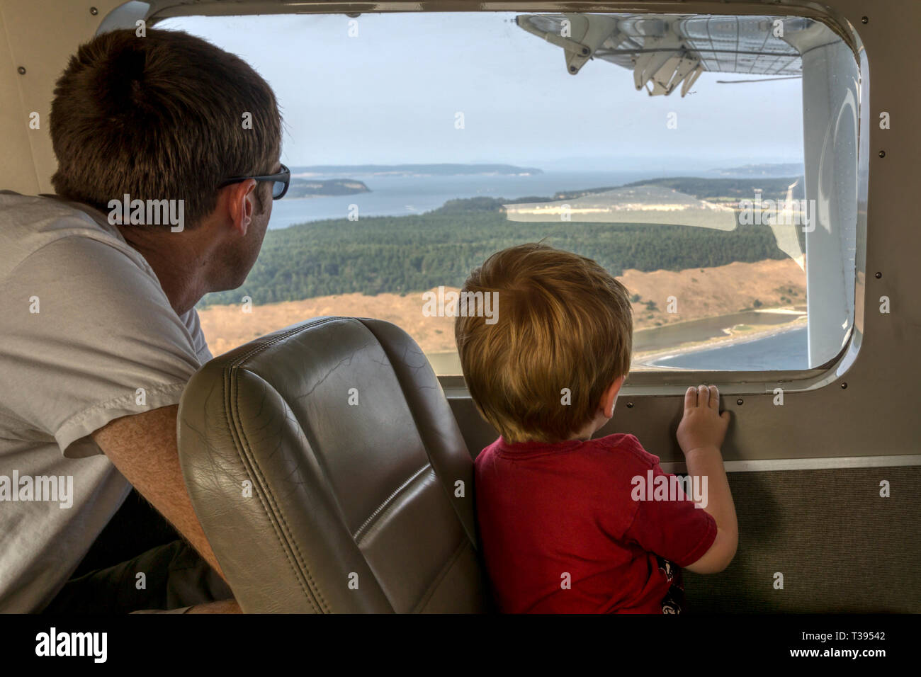 A father & son looking out of the window of a small float plane flying between Seattle and the San Juan Islands. Stock Photo