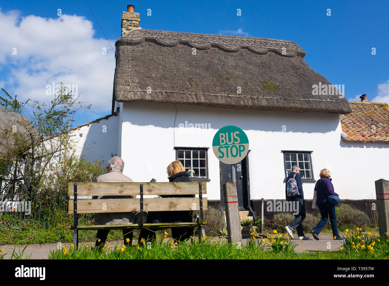 Thriplow, Cambridge, England, UK - March 2019: Senior old couple sitting on a wooden bench at a village bus stop with traditional British cottage - Stock Image