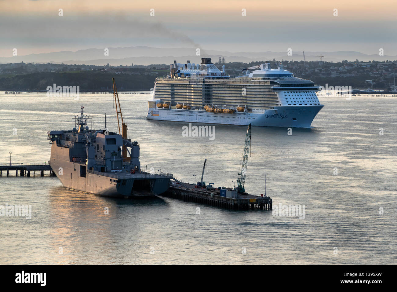 Ovation of the Seas in the Waitemata Harbour passing HMNZS Canterbury, Auckland, New Zealand,  Sunday, March 17, 2019.Photo: David Rowland / One-Image - Stock Image