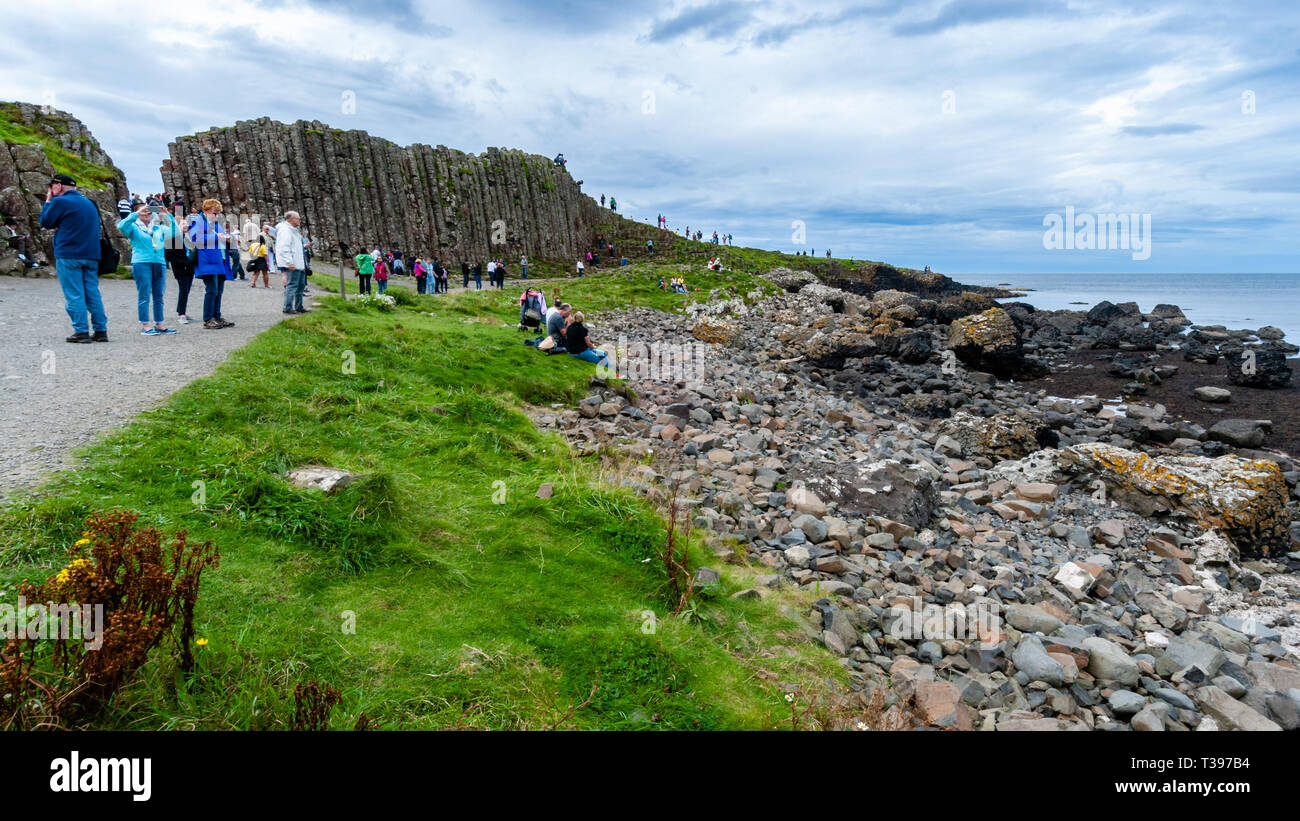 Tourists at the Giant's Causeway in Bushmills Northern Ireland. - Stock Image