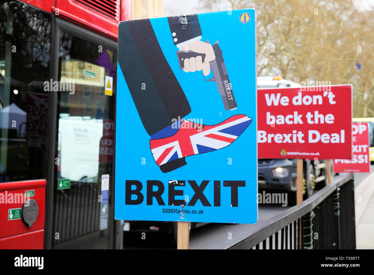 """Anti-Brexit SODEM gun Union Jack shoe poster  """"Shoot Yourself in the Foot""""  outside Parliament in Westminster, London UK 4 April 2019  KATHY DEWITT Stock Photo"""