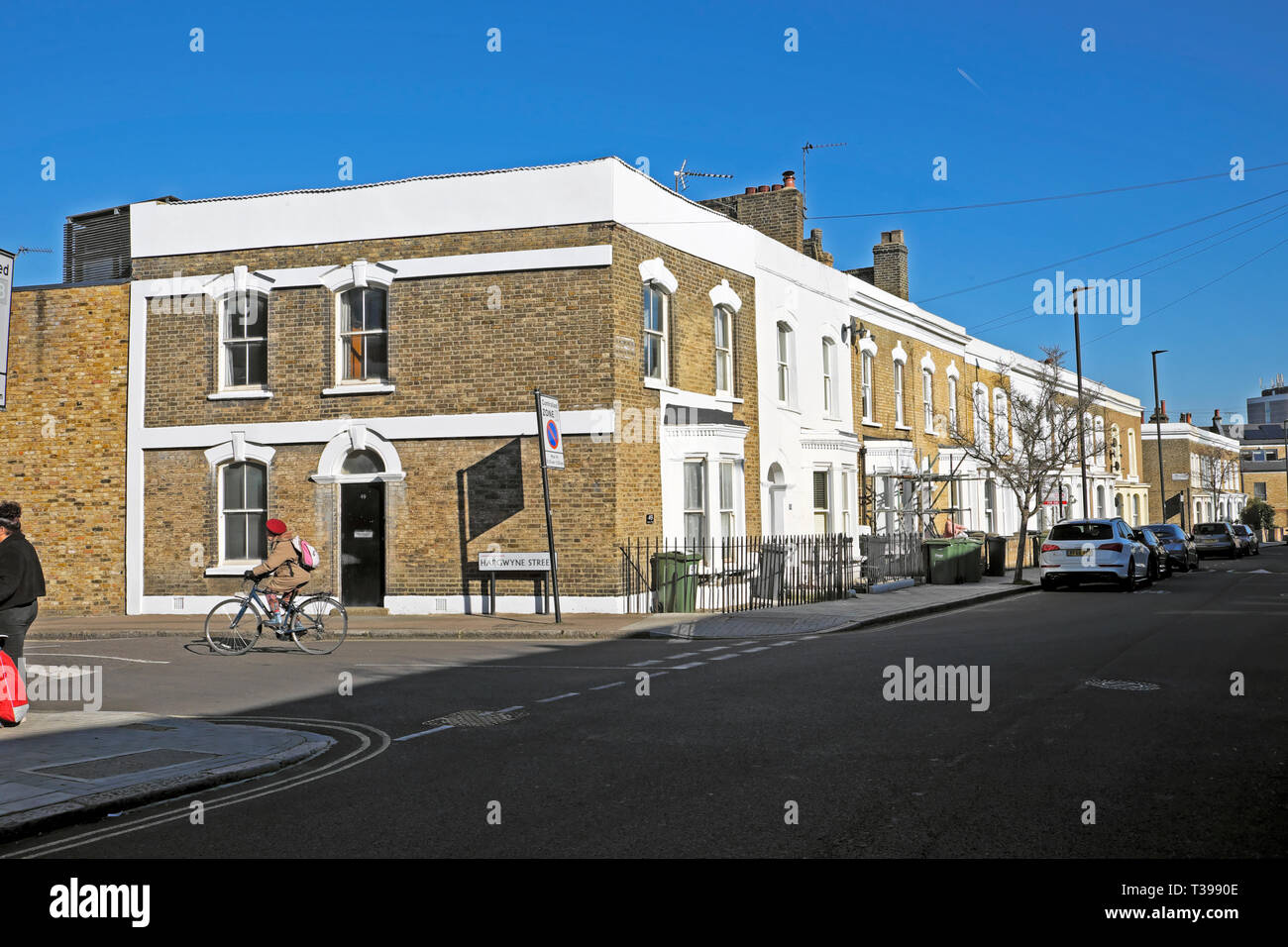 A woman riding a bike on Hargwyne Street and a row of terraced housing on Pulross Road in Brixton, South London SW9 England UK  KATHY DEWITT Stock Photo