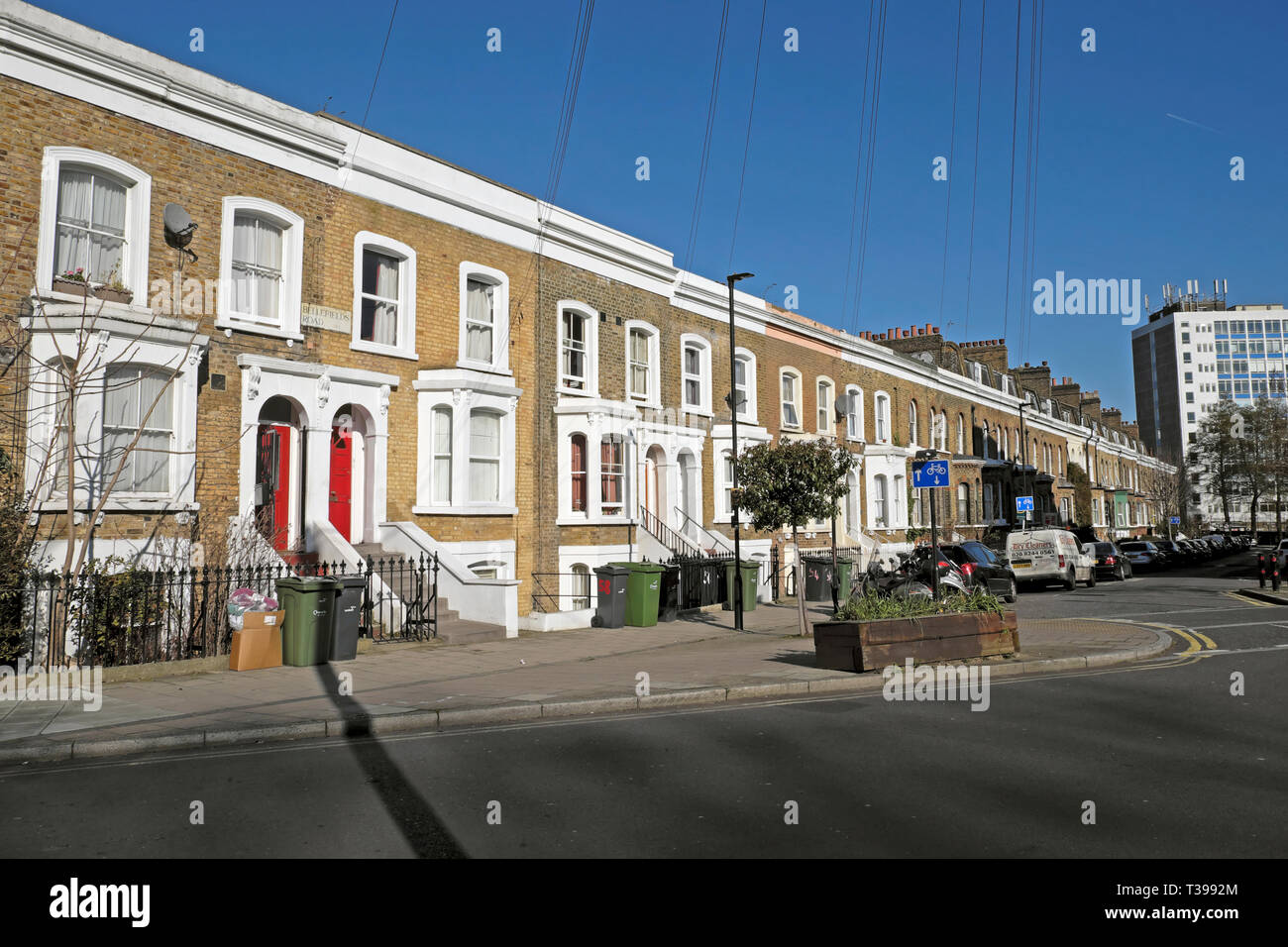 Row of terraced housing on Bellefirelds Road in Brixton with parked cars and rubbish bins outside houses, South London England UK  KATHY DEWITT Stock Photo