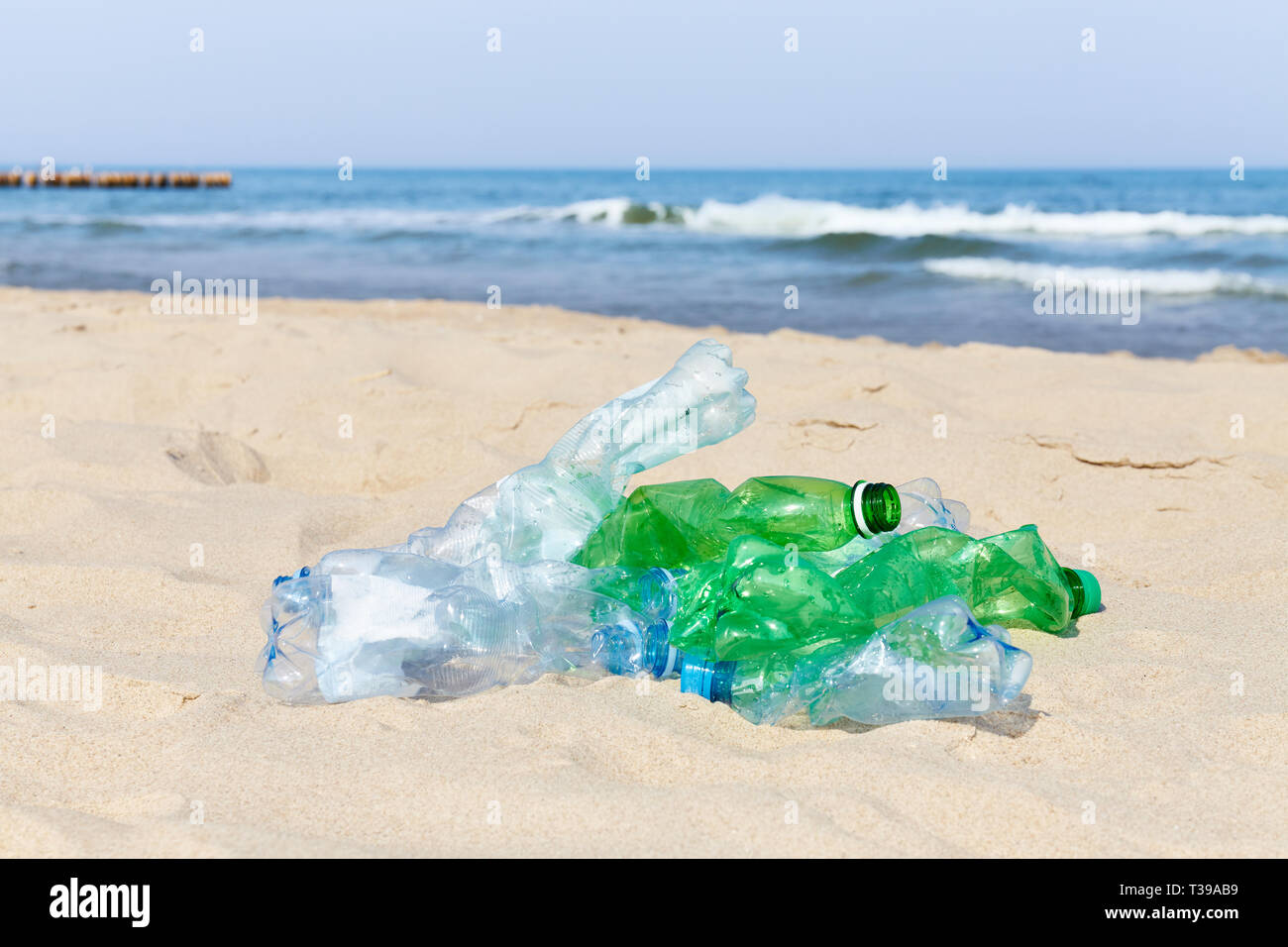 Used plastic bottles on a beach, selective focus. - Stock Image