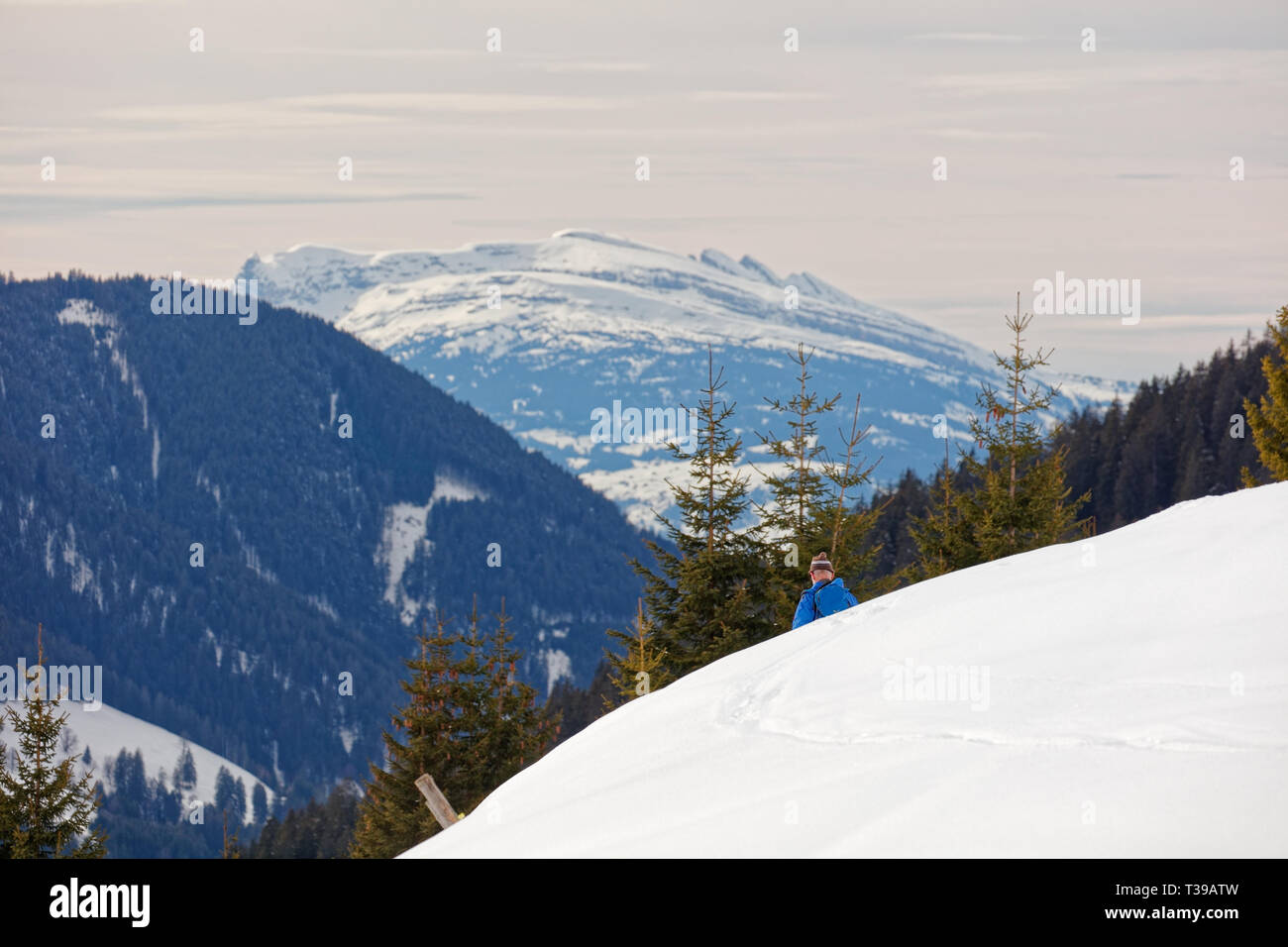 Ski tourist passing by with views from snow covered Furkajoch alpine road with Laternsertal valley and Appenzell Alps in background - Vorarlberg, Aust - Stock Image