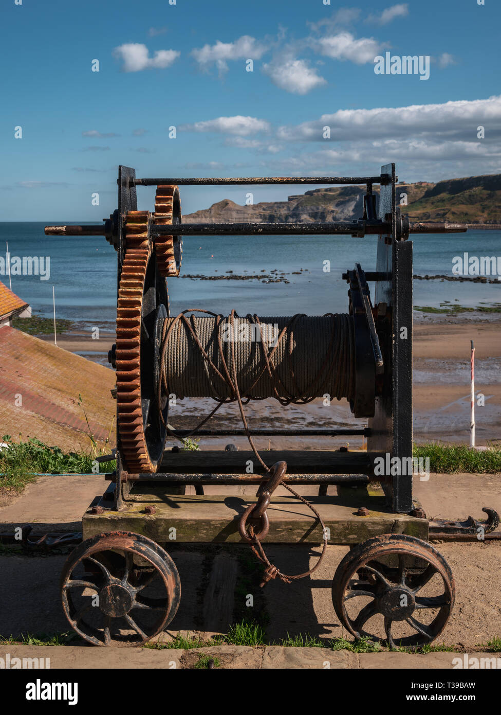 An old rope winch on the North Sea coast in Runswick Bay, North Yorkshire, England, UK - Stock Image