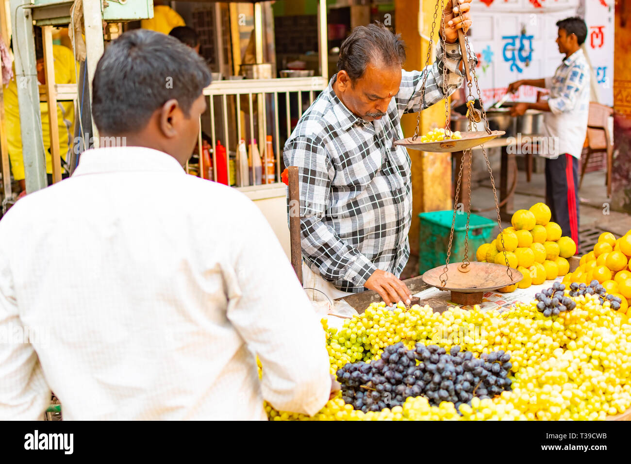ed7afe0594 India, Varanasi, Mar 10 2019 - Unidentified vendor man sells and weighs  grapes on
