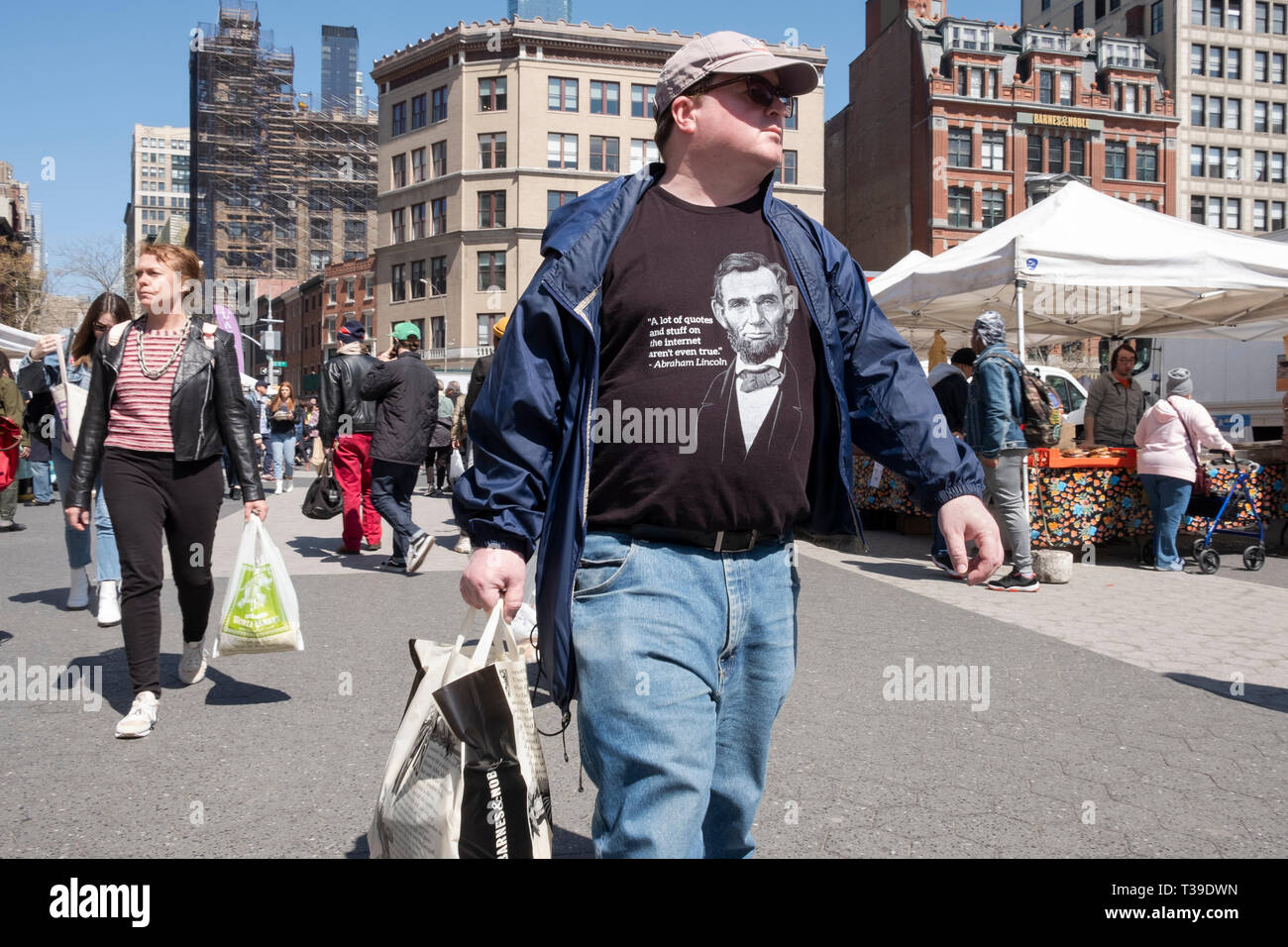 A young man shopping and wearing an Abraham Lincoln t shirt warning that not all of the internet is true. At the Union Square Green Market in New York - Stock Image
