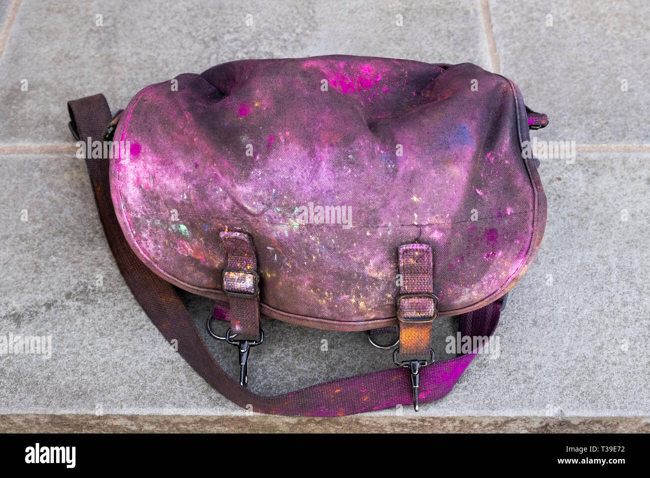 A Domke camera bag soiled by the colored powder thrown at the 2019 Holi Parade in Richmond Hills, Queens, New York City. - Stock Image