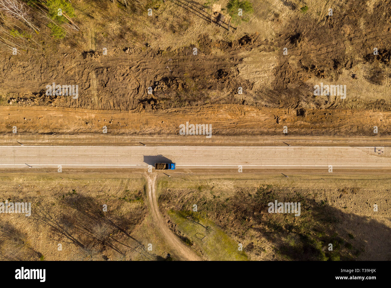 Drone view of truck and road repair work in rural landscape. Drone photography. - Stock Image
