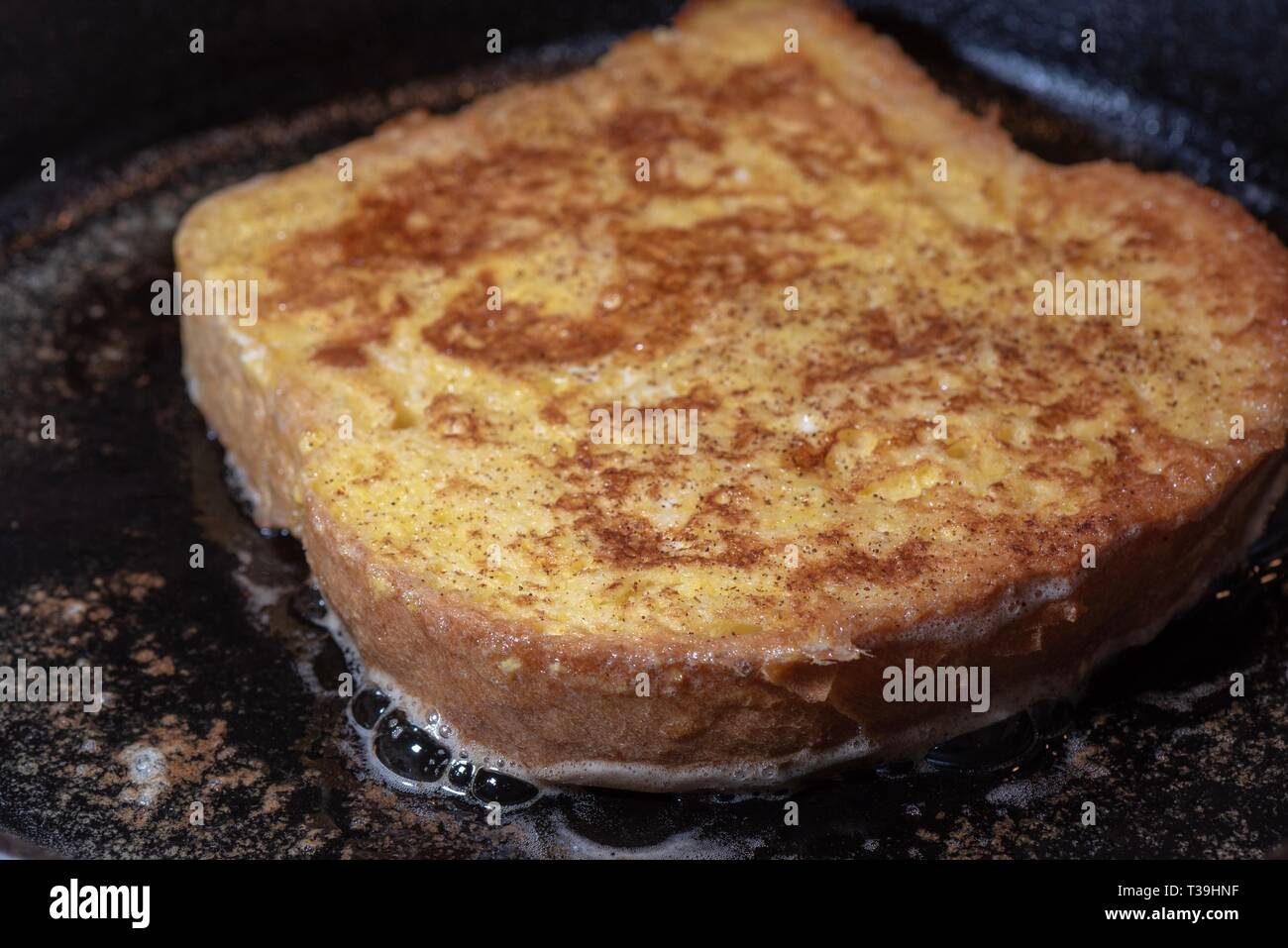 Making breakfast French toast in cast iron frying pan. Stock Photo