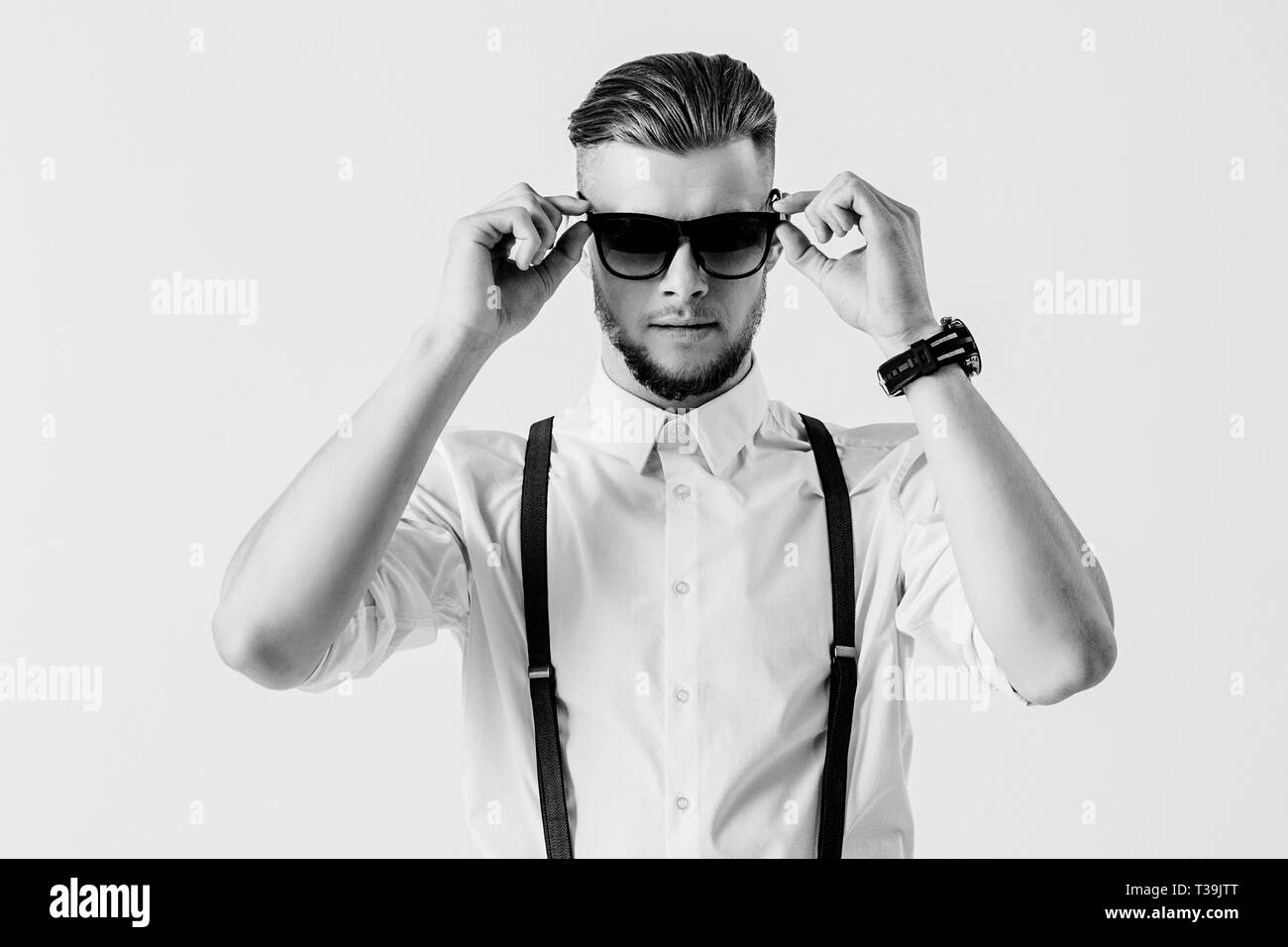 Black and white shot of stylish and elegant man in shirt with suspenders wearing sunglasses while standing against white background. Fashionable man i - Stock Image