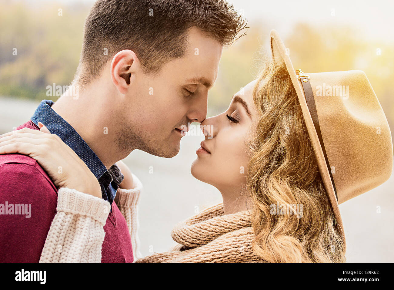 Totally in love. Cropped image of young beautiful couple keeping eyes closed while standing close face to face. Young couple in love walking outdoors. Stock Photo