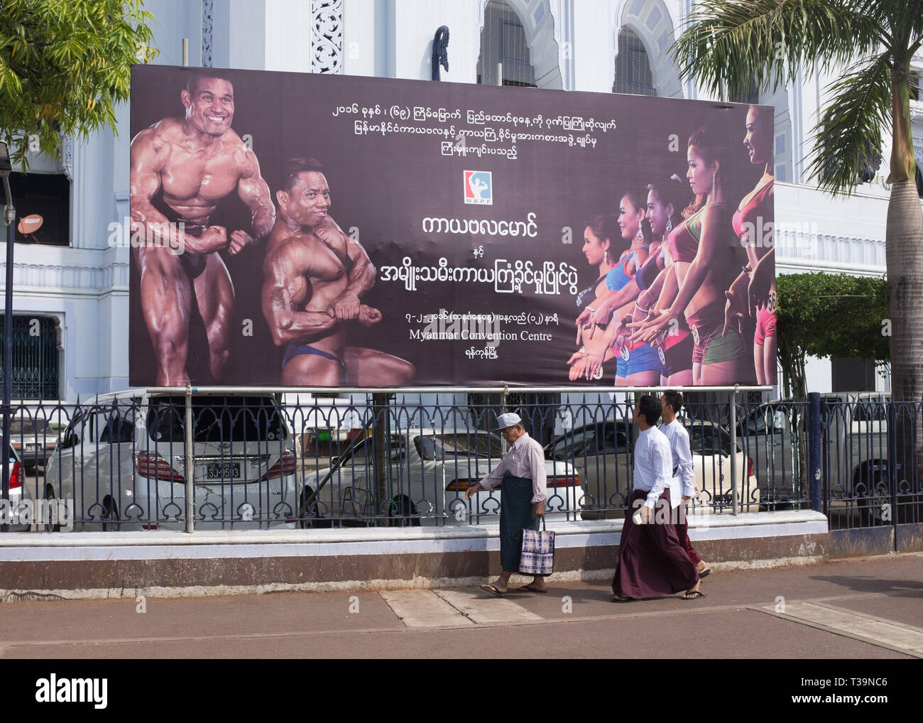 Men walking past a billboard advertising body building on Sule Pagoda Roundabout in Yangon (Rangoon), Myanmar (Burma) Stock Photo