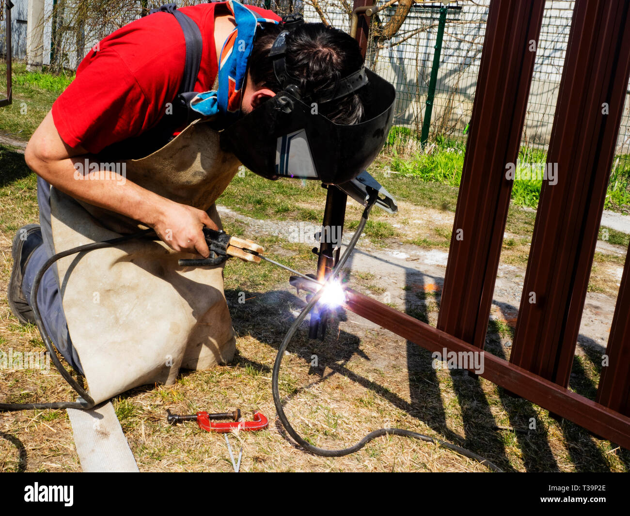 Man is welded to a steel gate metal latch Stock Photo