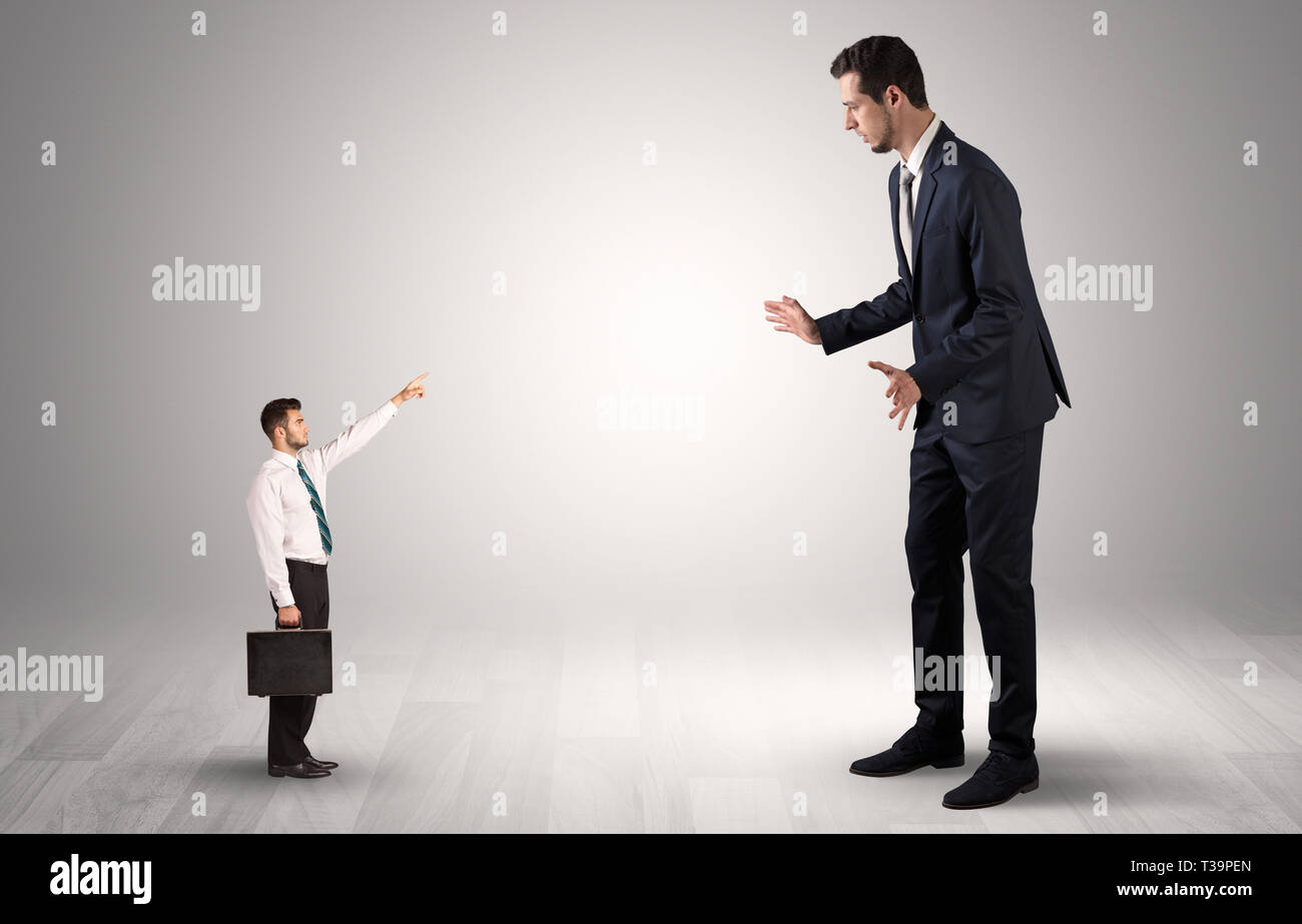 Small businessman in shirt pointing to an afraid businessman  - Stock Image