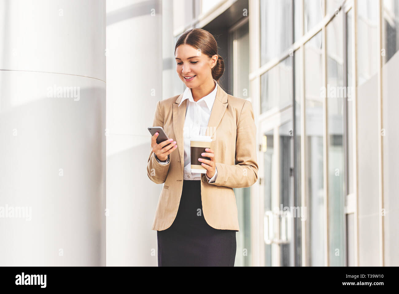 Always in touch with colleagues. Portrait of young and beautiful business woman in suit using her smart phone and keeping cup of coffee in hand while  - Stock Image