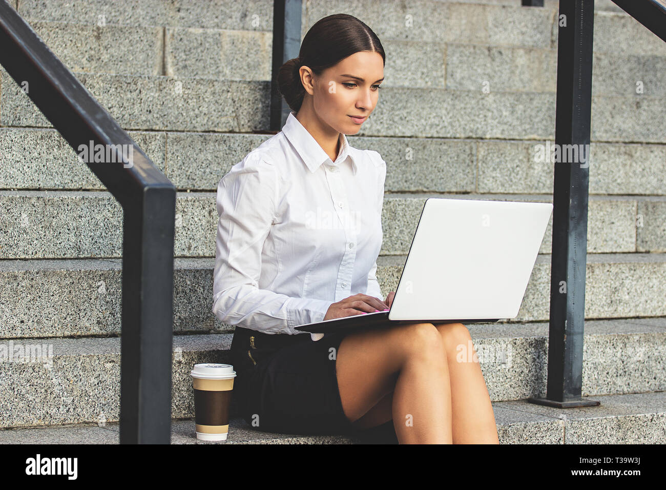 Time to work outdoors. Side view of confident, young and attractive woman in formal wear working on her laptop while sitting on office stairs. Cup of  - Stock Image