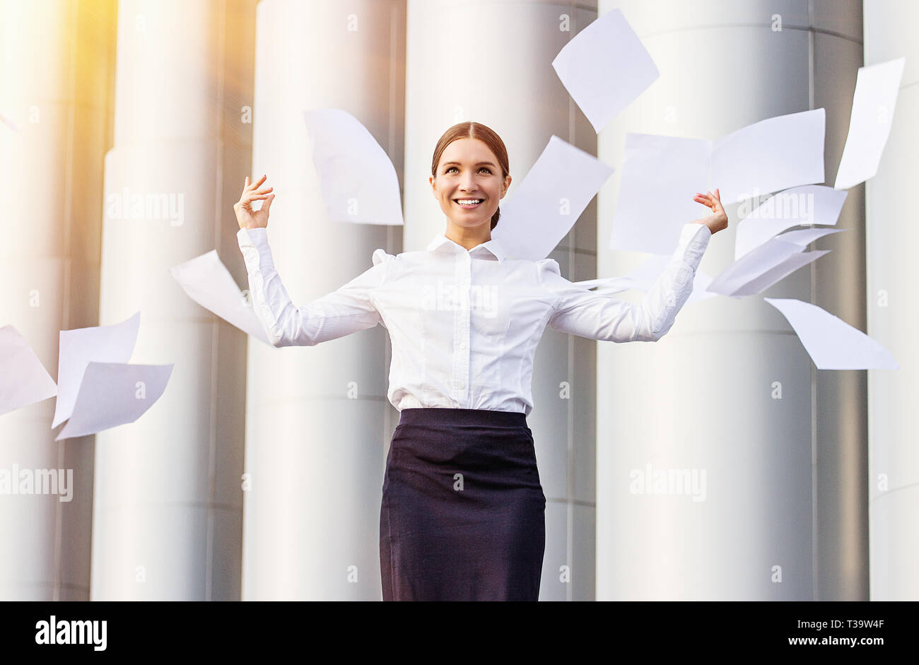 Celebrating success. Portrait of young and beautiful business woman in skirt and shirt throwing up papers and smiling while standing against white pil - Stock Image