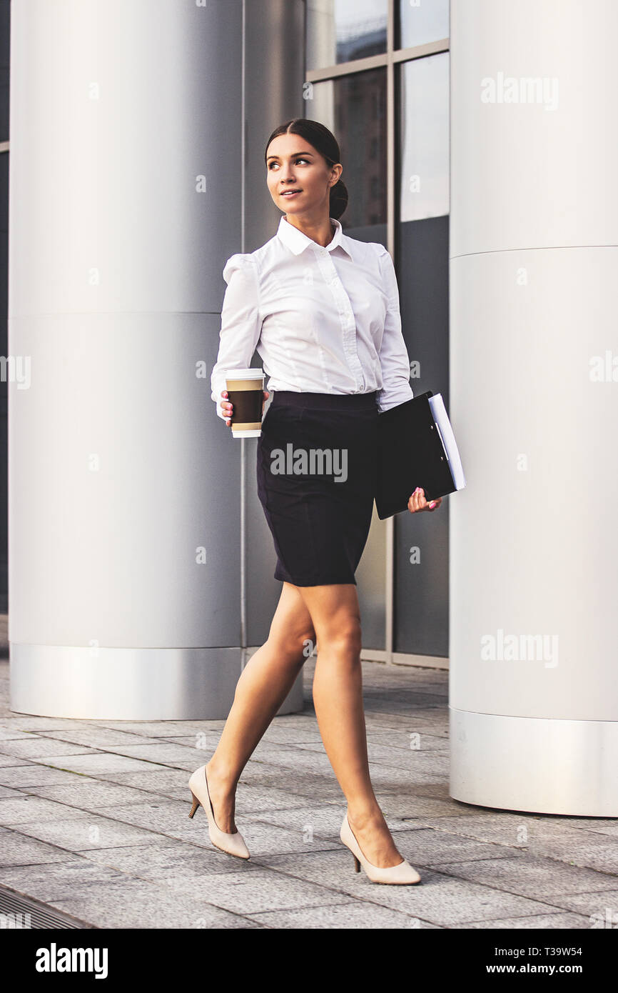 Business on the move. Beautiful and young business woman looking away and keeping cup of coffee in one hand and folder with documents in another while - Stock Image