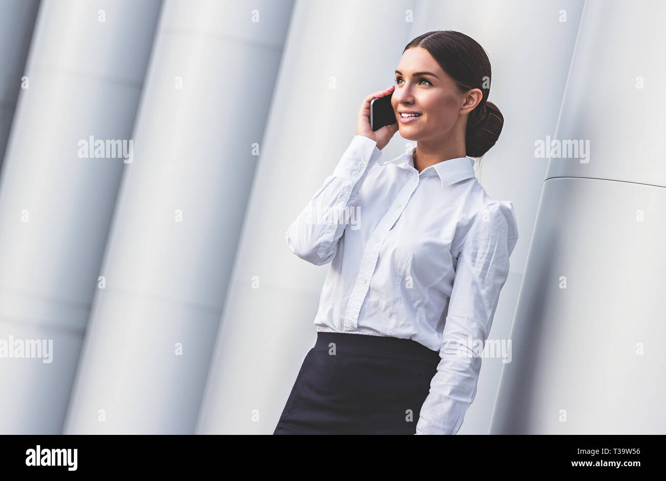 Sharing good news. Low-angle view of attractive and young business woman in formal wear talking on her smart phone and smiling while standing outdoors - Stock Image
