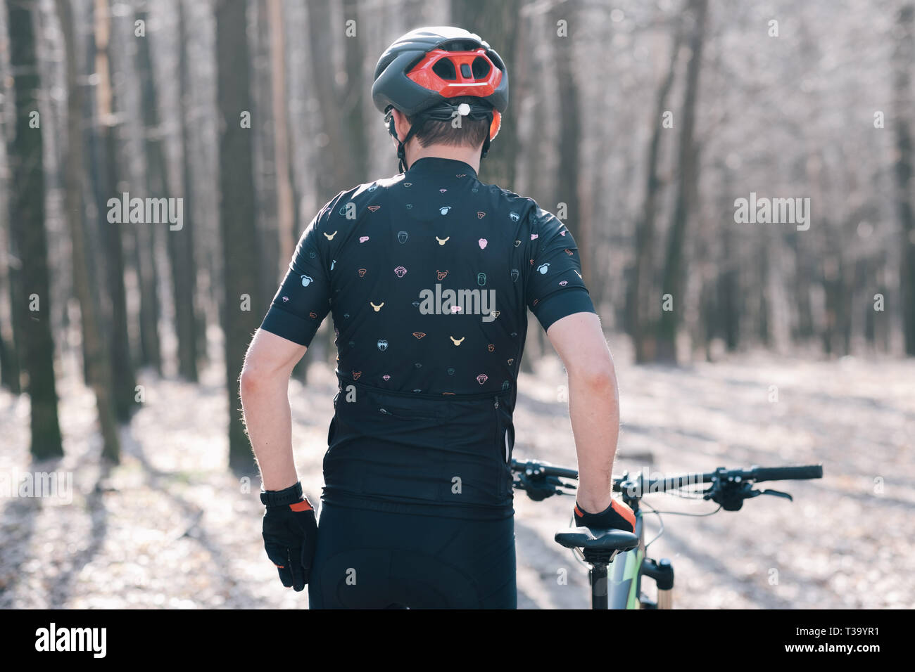 male athlete mountainbiker rides with bicycle in the forest - Stock Image