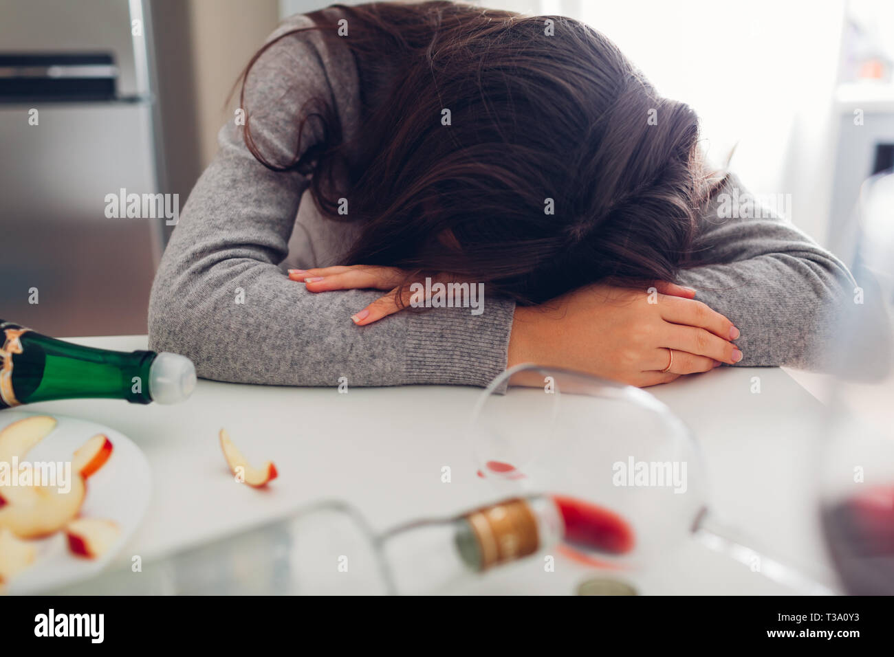Female alcohol addiction. Young woman sleeping on kitchen table surrounded with wine bottles. Alcoholism Stock Photo