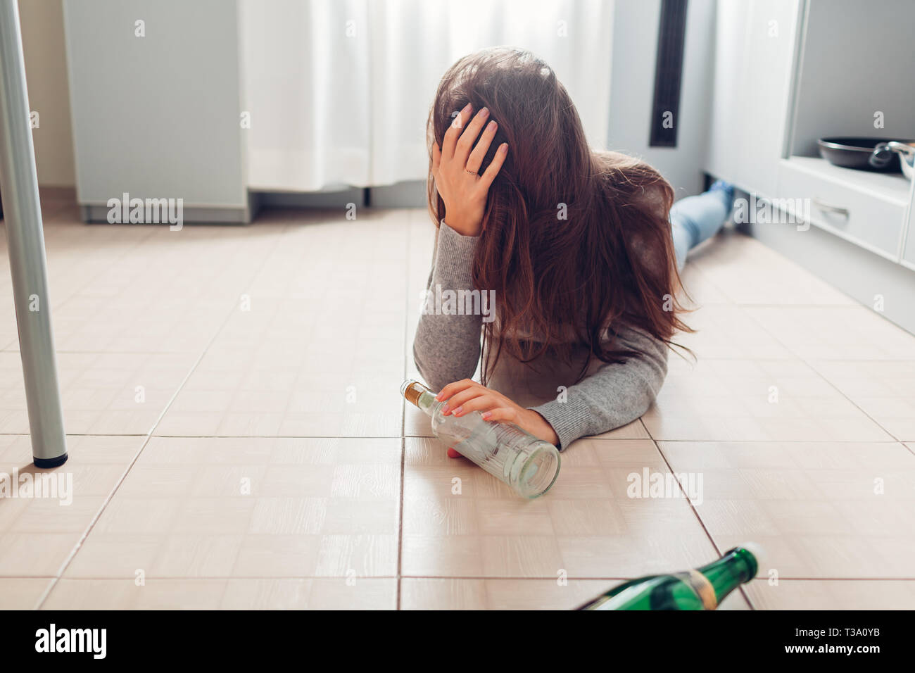 Female alcohol addiction. Young woman woke up on kitchen floor after party surrounded with wine bottles and having hangover - Stock Image