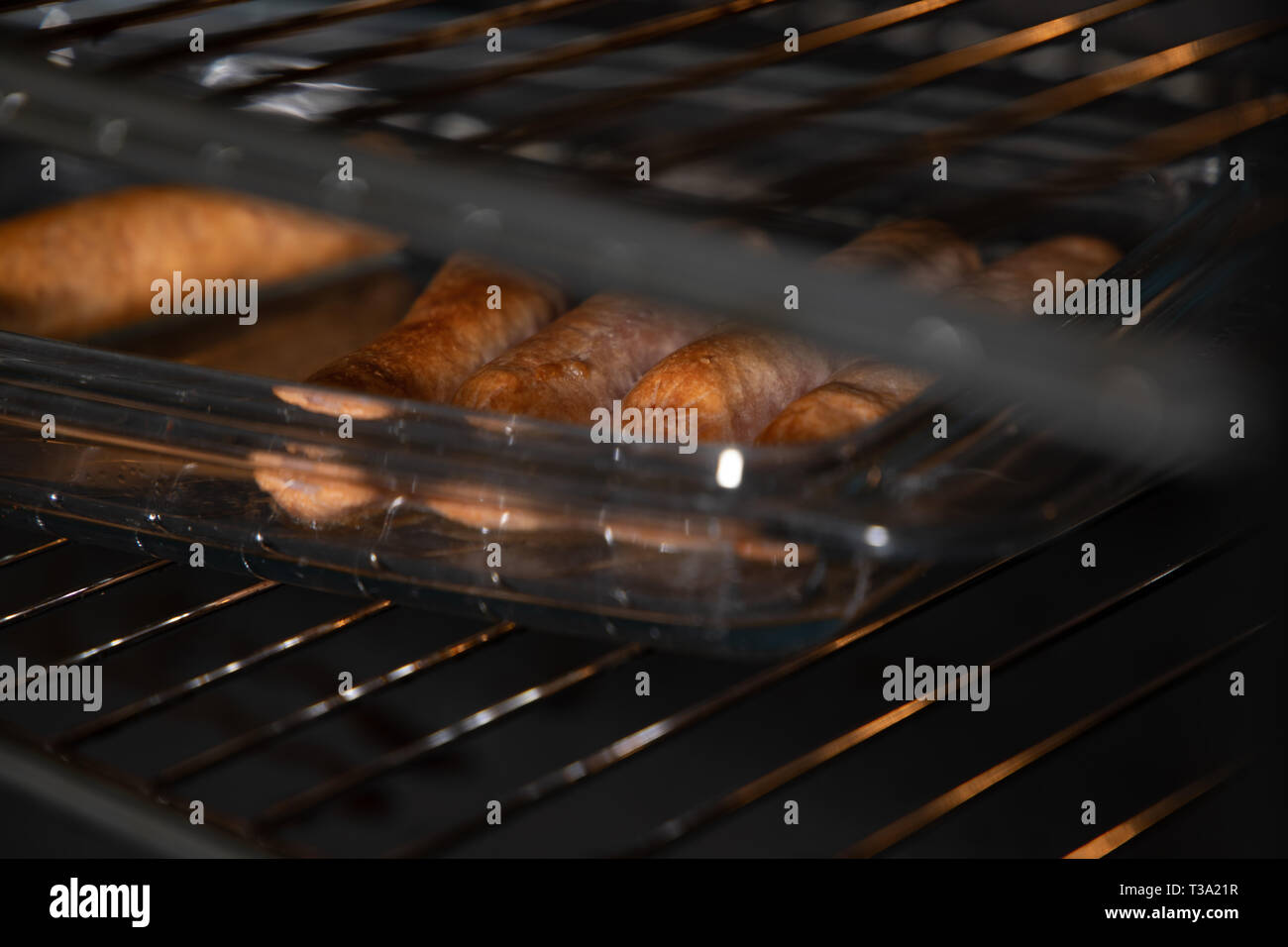 Sausages being baked in the oven - Stock Image
