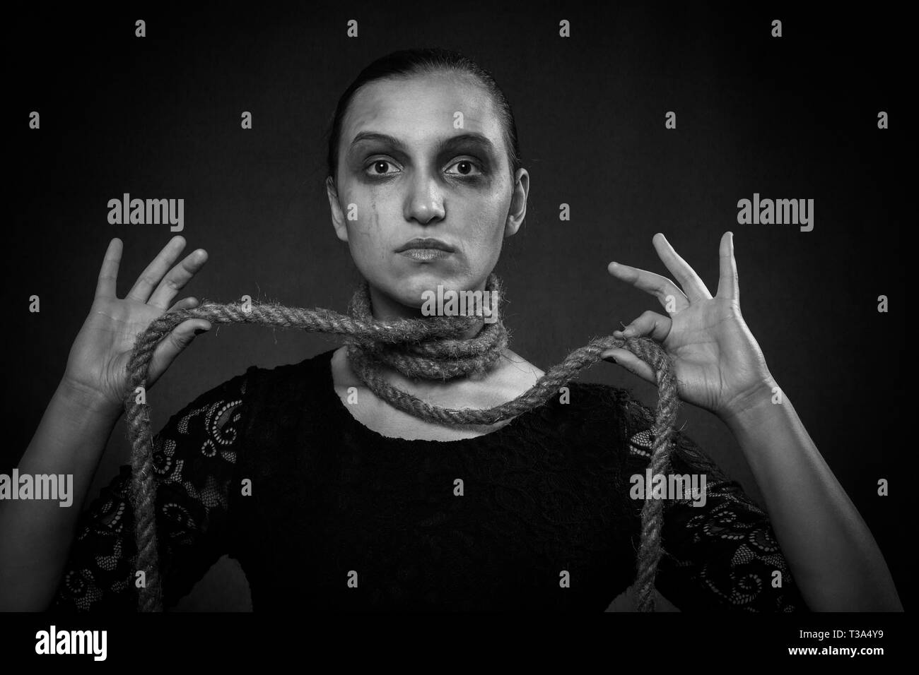 serious woman with rope on neck at black background looking at camera - Stock Image