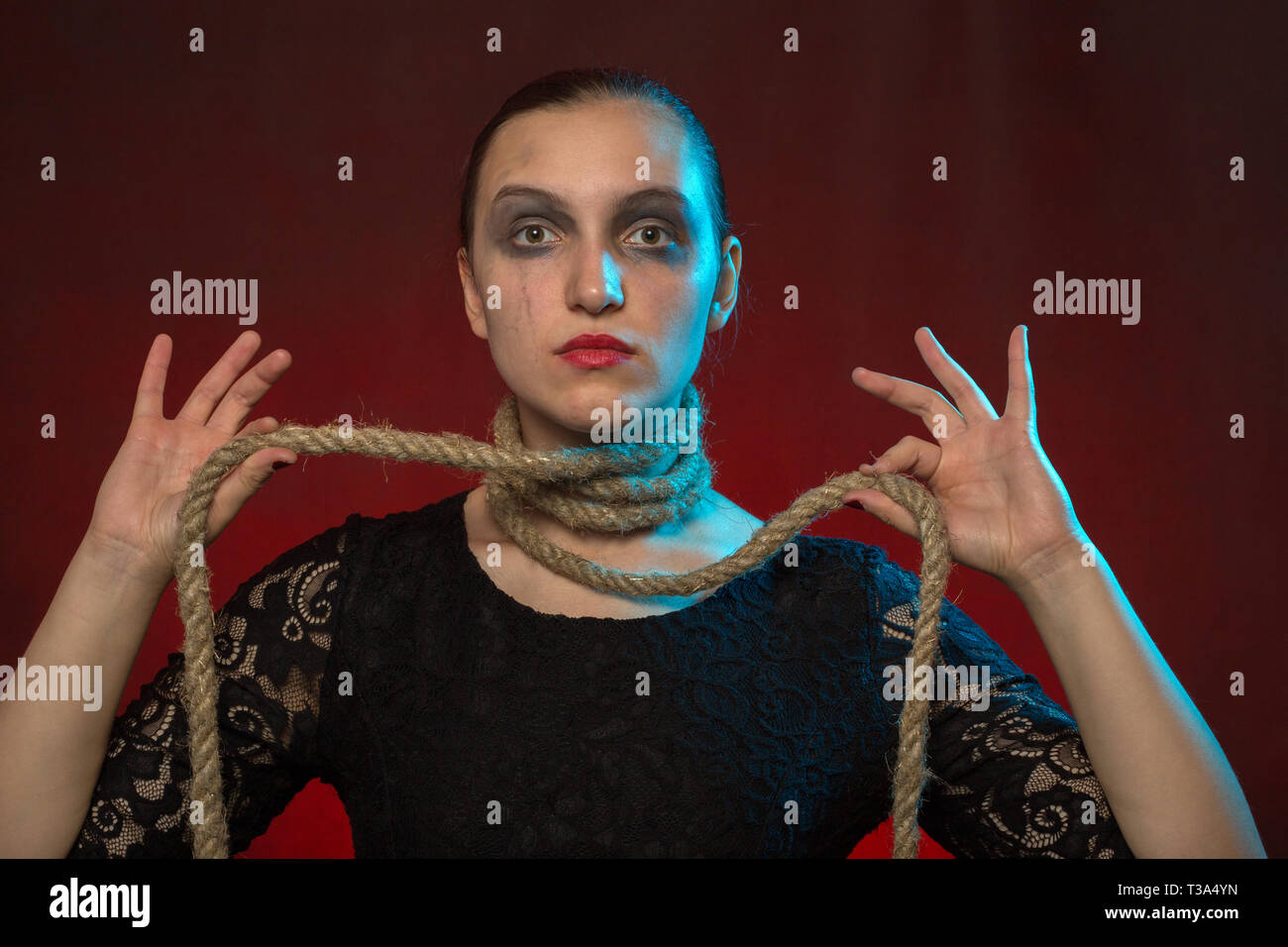 serious woman with rope on neck at red background looking at camera - Stock Image