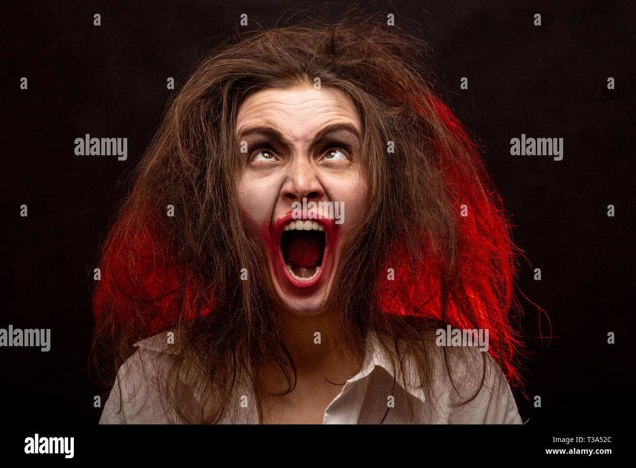 fun crazy young woman with fluffy hair on black background make grimace screaming - Stock Image