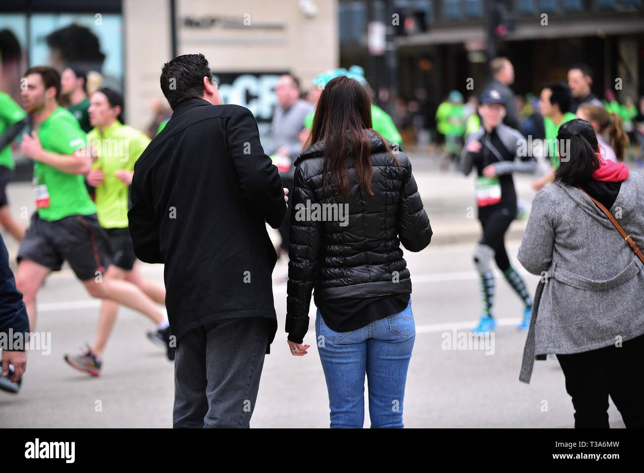 Chicago, Illinois, USA. A group of runners passing by spectators along Michigan Avenue during the 2019 Shamrock Shuffle race in Chicago. The annual 8K - Stock Image