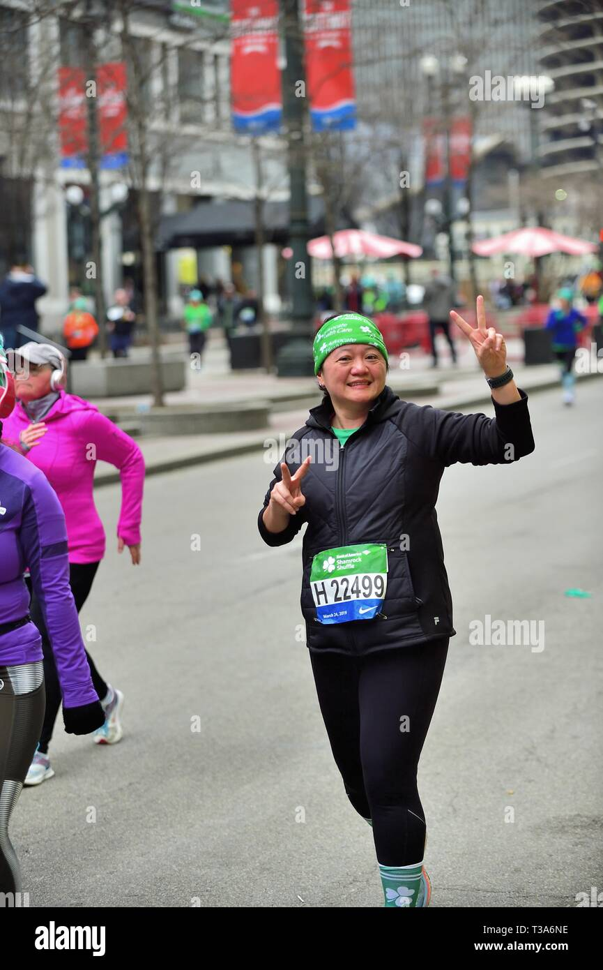 Chicago, Illinois, USA. A woman progressing down State Street during the 2019 Shamrock Shuffle race flashes a victory sign to a supporter in the crowd. - Stock Image