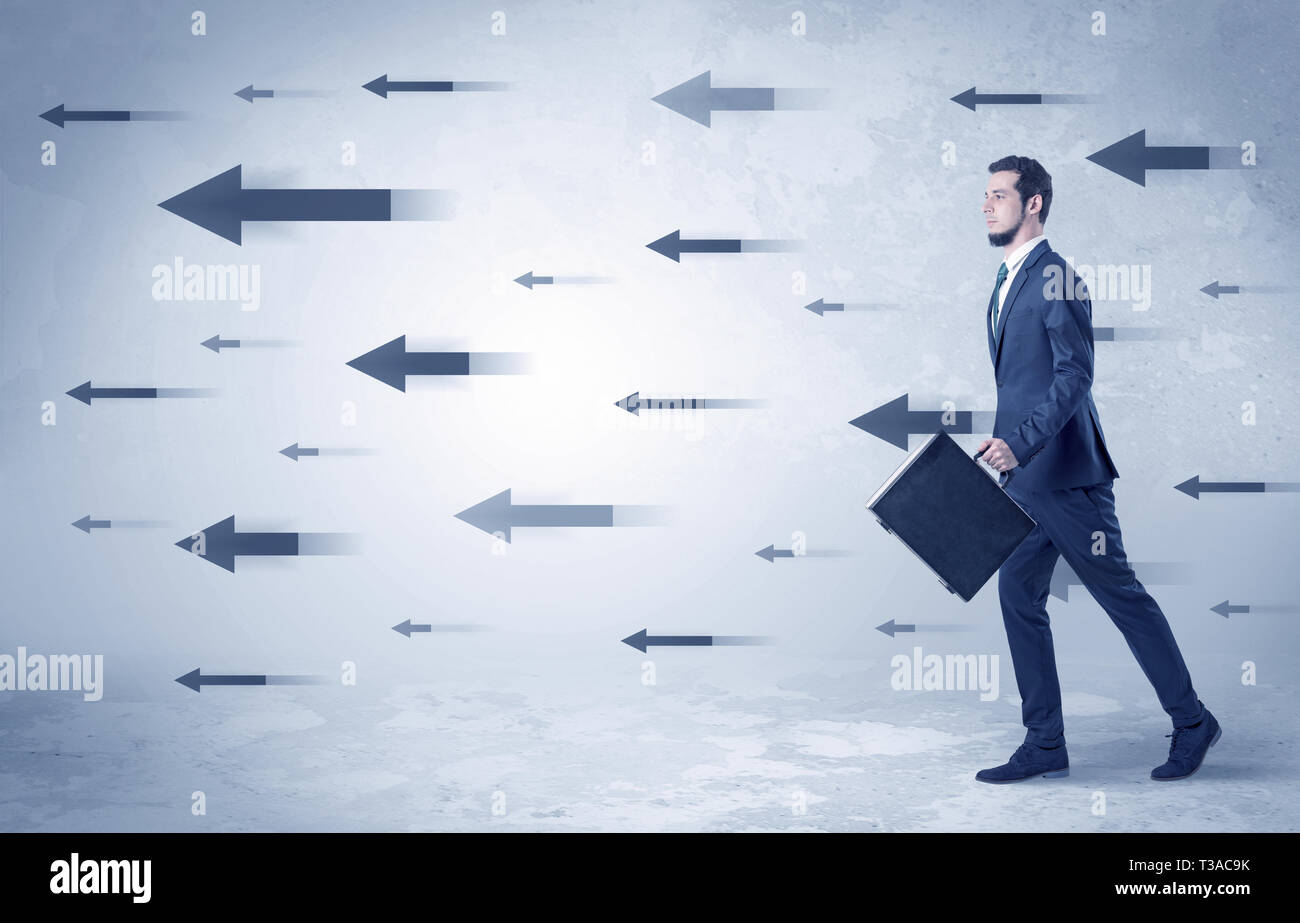 Businessman walking with arrows on the background and briefcase on his hand  - Stock Image