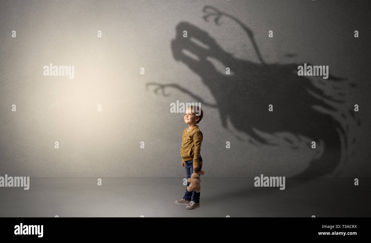 Scary ghost shadow in a dark empty room with a cute blond child  - Stock Image
