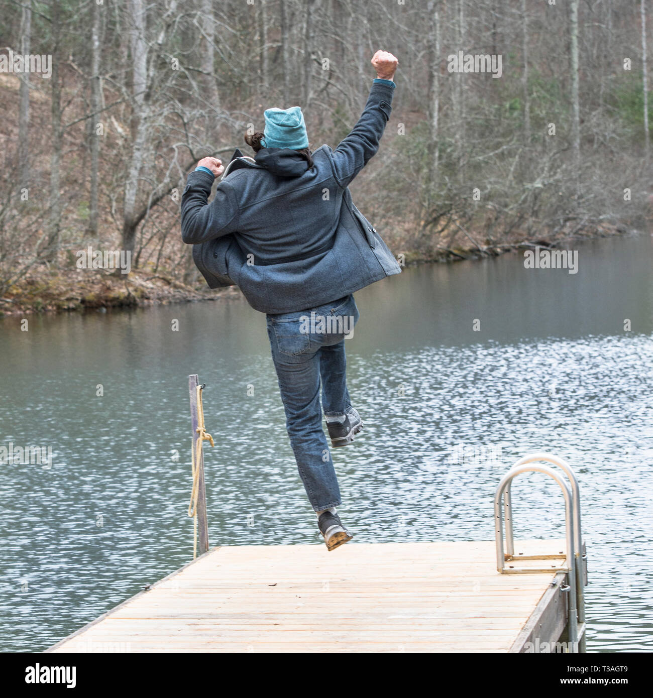 Jumping for joy, a man expresses exuberance by taking a leap into the air,  punching arm into the air. Viewing his back. - Stock Image