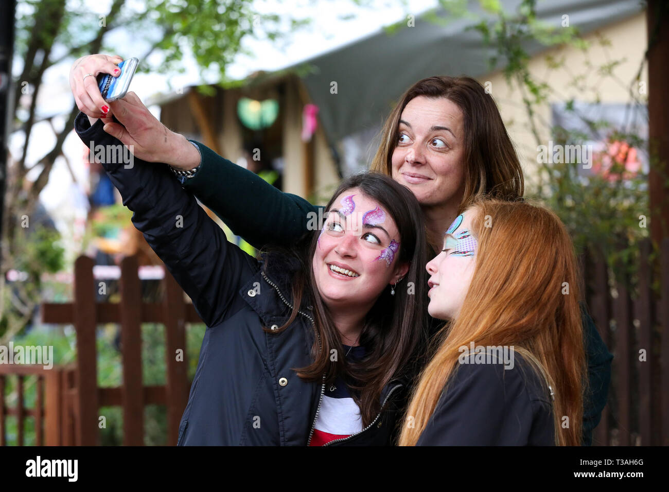 Spectators are seen taking a selfie before the Oxford vs Cambridge Goat Race in East London. Two pygmy goats compete during the 10th Oxford and Cambridge Goat Race at Spitalfields City Farm, Bethnal Green in East London. The annual fundraising event, which takes place at the same time as the Oxford and Cambridge boat race, where two goats, one named Hamish representing Oxford and the other Hugo representing Cambridge to be crowned King Billy. - Stock Image
