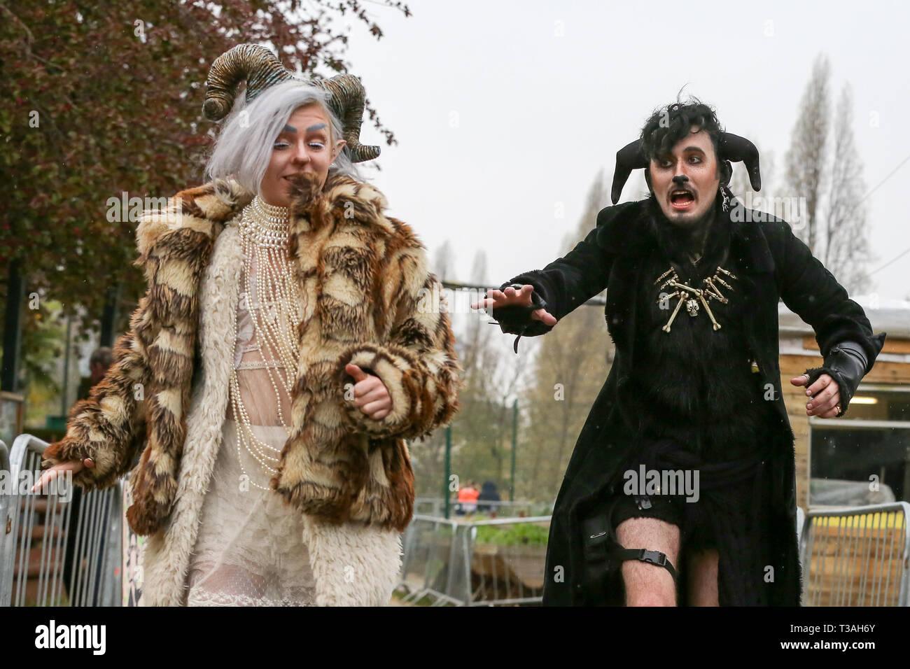 People dressed in goats outfits are seen running before the Oxford vs Cambridge Goat Race in East London. Two pygmy goats compete during the 10th Oxford and Cambridge Goat Race at Spitalfields City Farm, Bethnal Green in East London. The annual fundraising event, which takes place at the same time as the Oxford and Cambridge boat race, where two goats, one named Hamish representing Oxford and the other Hugo representing Cambridge to be crowned King Billy. - Stock Image