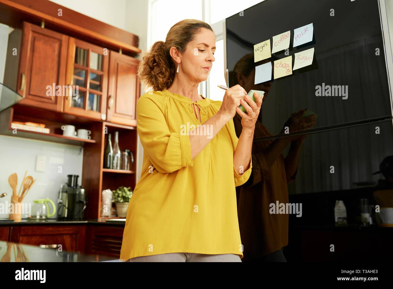 Housewife sticking notes on fridge - Stock Image