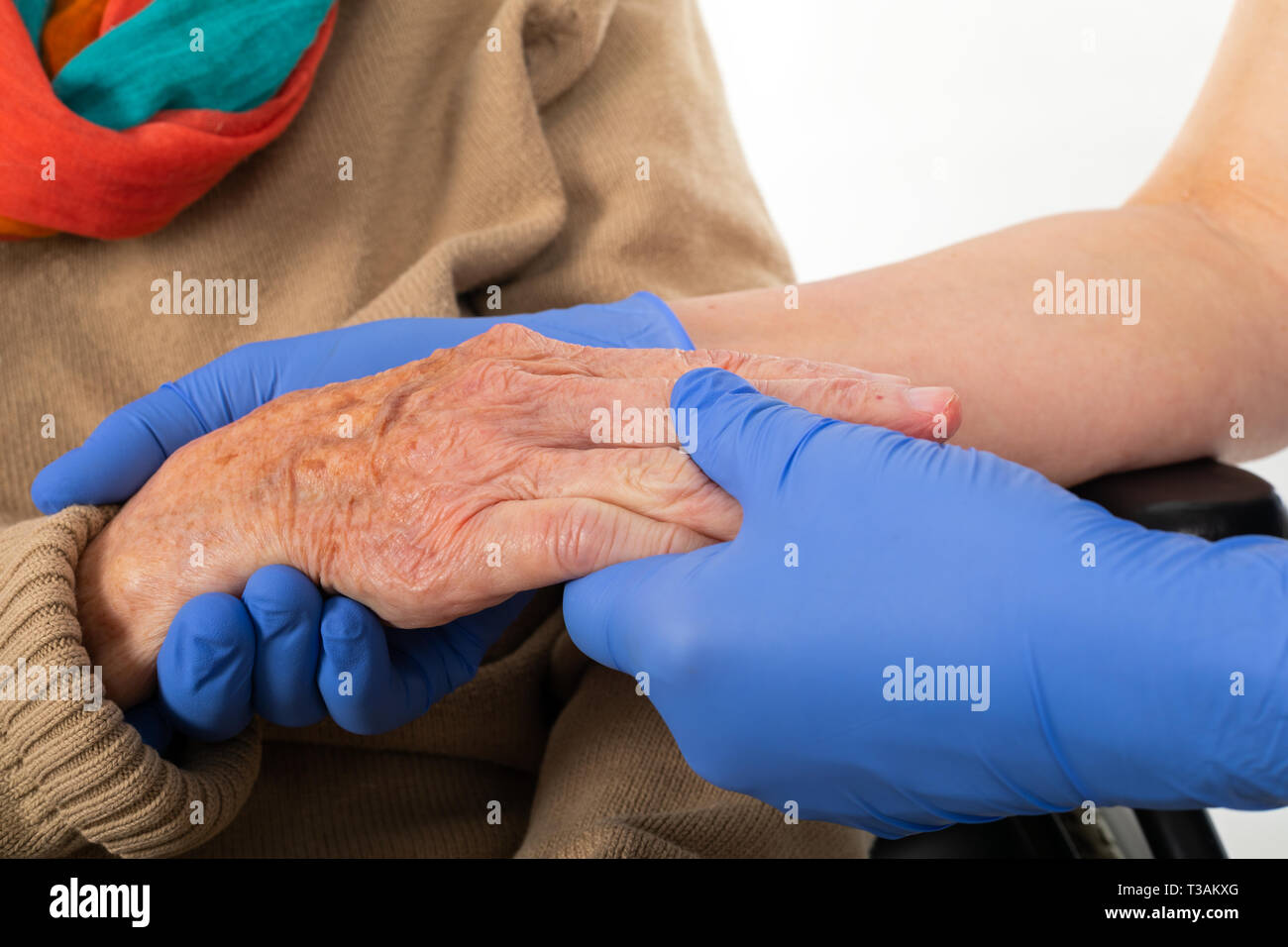 Close up picture of medical nurse wearing blue sterile gloves holding old disabled woman's hands - Stock Image