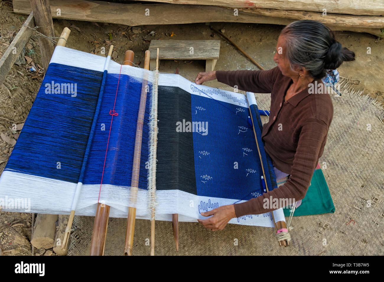 Old woman weaving by loom in Chakma tribal village, Rangamati, Chittagong Division, Bangladesh - Stock Image