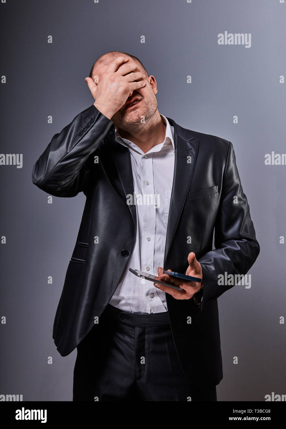 Unhappy stressed depressed business man holding in hand two mobile phones and covering the face the palm in office suit on grey background. Closeup po Stock Photo