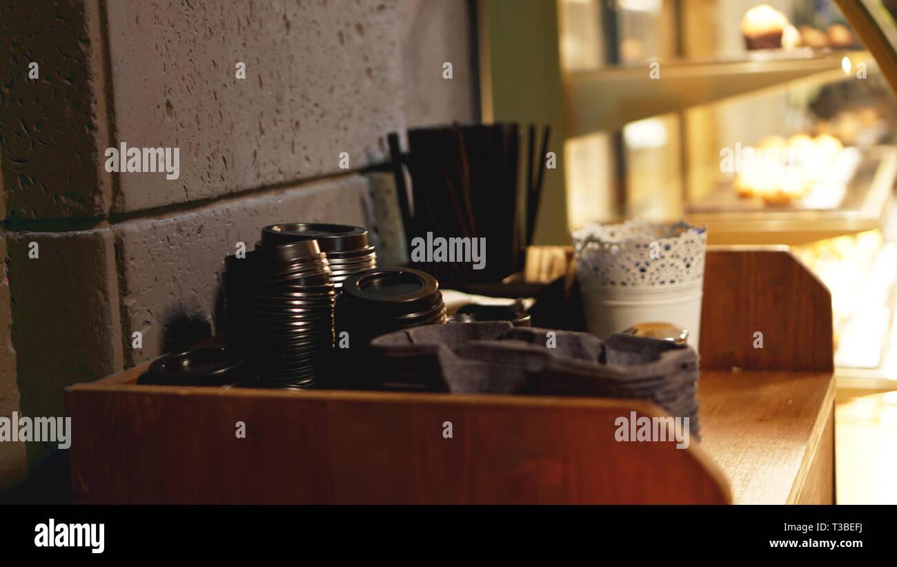 A stack of plastic caps and tubes for coffee. The self-service area in the coffee shop in brown tones - blurred background. - Stock Image